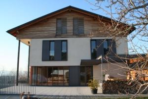 Holzhaus Schiebeläden außen braun grau